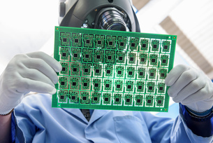 Worker inspecting circuit boards in circuit board assembly factory, close upの写真素材 [FYI03554379]