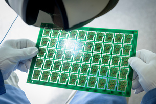 Worker inspecting circuit boards in circuit board assembly factory, close upの写真素材 [FYI03554380]