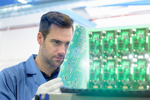 Worker inspecting circuit boards in circuit board assembly factoryの写真素材 [FYI03554382]