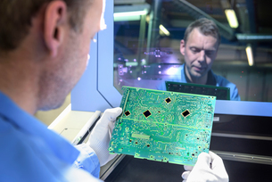 Worker inspecting circuit boards in circuit board assembly factoryの写真素材 [FYI03554383]