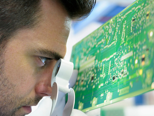 Worker inspecting circuit boards in circuit board assembly factory, close upの写真素材 [FYI03554384]