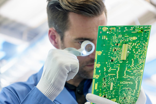 Worker inspecting circuit boards in circuit board assembly factoryの写真素材 [FYI03554385]