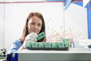 Female worker inspecting circuit boards in circuit board assembly factoryの写真素材 [FYI03554386]