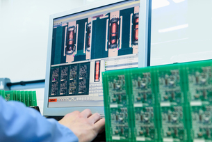Worker testing circuit boards in circuit board assembly factory, close upの写真素材 [FYI03554394]