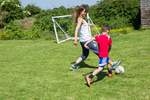 Mother and son playing football in the gardenの写真素材 [FYI03554404]