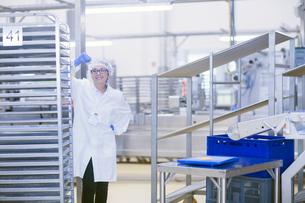 Factory worker wearing hair net looking at camera smilingの写真素材 [FYI03554443]