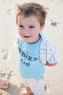 Boy on beach, hands behind back looking away smilingの写真素材 [FYI03554477]