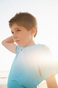 Boy with hand on head looking awayの写真素材 [FYI03554482]