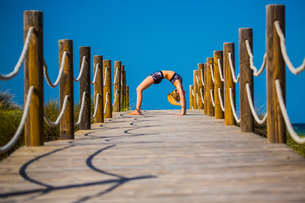 Young woman on wooden pathway, exercising, bent over backwardsの写真素材 [FYI03554525]
