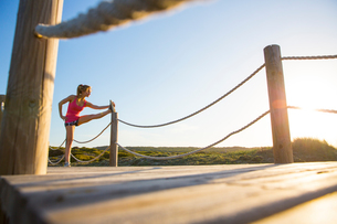 Young woman on wooden pathway, exercising, stretching leg, low angle viewの写真素材 [FYI03554537]