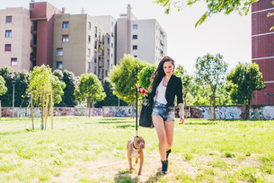 Young woman walking pit bull terrier in urban parkの写真素材 [FYI03554654]