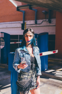 Young woman with dip dyed blue hair using smartphone in urban housing estateの写真素材 [FYI03554660]