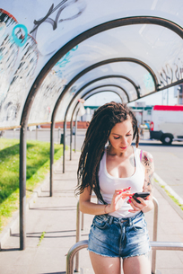 Young woman with dreadlocks using smartphone touchscreen in urban bus shelterの写真素材 [FYI03554673]