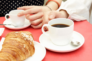 Close up of women's hands having black coffee and croissants at sidewalk cafeの写真素材 [FYI03554699]