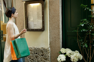 Woman with shopping bags reading menu outside restaurant, Milan, Italyの写真素材 [FYI03554716]