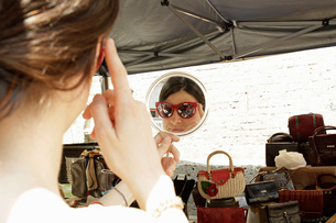 Mirror image of woman trying on sunglasses at market stall, Milan, Italyの写真素材 [FYI03554724]