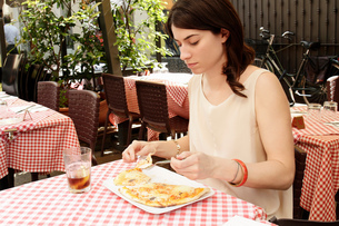 Woman at sidewalk cafe eating pizza, Milan, Italyの写真素材 [FYI03554728]