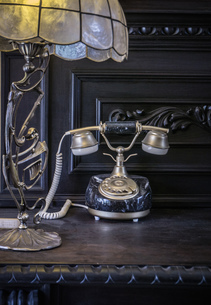 Art deco lamp and vintage telephone on antique sideboardの写真素材 [FYI03554763]