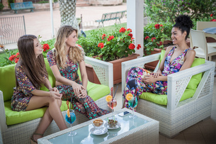 Three young women relaxing on apartment patio talking, Costa Rei, Sardinia, Italyの写真素材 [FYI03554772]
