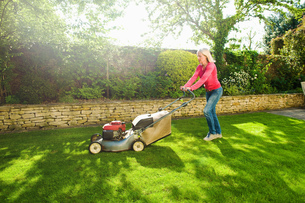 Mature woman mowing sunlit garden lawn with lawn mowerの写真素材 [FYI03554802]