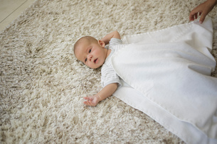 Swaddling Step 3. Mothers hands covering baby boy with blanketの写真素材 [FYI03554943]