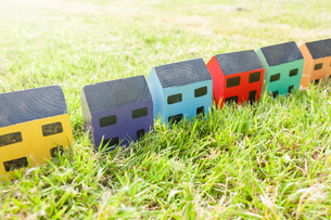 Row of wooden toy houses on grassの写真素材 [FYI03554959]
