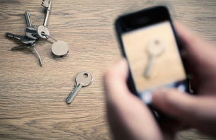 Man's hands taking photograph with smartphone of bunch of keysの写真素材 [FYI03554964]