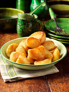 Roast potatoes in vintage green bowl, plates and fork, rustic wooden tableの写真素材 [FYI03554967]