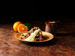 Christmas pudding with liqueur and orange sauce on gold plate, oranges, vintage pot of sauceの写真素材 [FYI03554979]