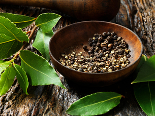 Crushed peppercorns in bowl, bay leaves on rustic wooden surfaceの写真素材 [FYI03554984]