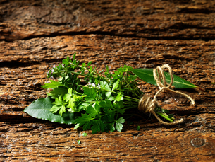 Parsley, thyme, bay leaves tied together with string on rustic wooden surfaceの写真素材 [FYI03554985]
