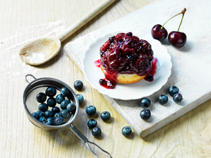 Morello cherry and blueberry sponge, fresh cherries and blueberries, wooden spoon with flour, whiteの写真素材 [FYI03554997]