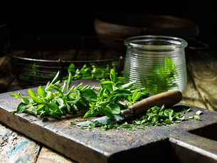 Marjoram, whole and chopped, some in glass jar, vintage knife, rustic wooden chopping boardの写真素材 [FYI03555001]