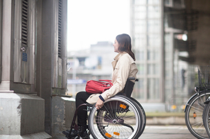 Young woman using wheelchair waiting for city elevatorの写真素材 [FYI03555115]
