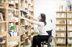 Young female shop assistant using wheelchair tidying up shop shelvesの写真素材 [FYI03555119]