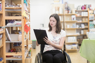 Young female shop assistant using wheelchair stocktaking in shopの写真素材 [FYI03555120]