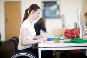 Young female university student using wheelchair reading notes at deskの写真素材 [FYI03555121]