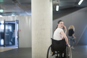 Young woman using wheelchair in underground parking lot talking on smartphoneの写真素材 [FYI03555122]