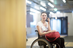 Portrait of young woman using wheelchair talking on smartphoneの写真素材 [FYI03555124]
