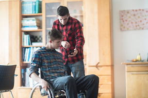 Young man using wheelchair reading smartphone texts with friend in kitchenの写真素材 [FYI03555125]