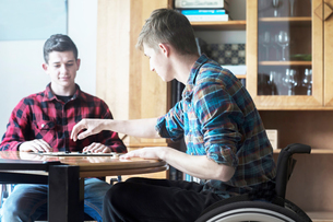 Young man using wheelchair playing draughts with friend in kitchenの写真素材 [FYI03555130]