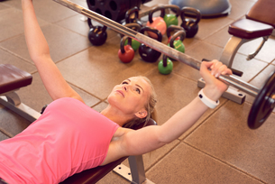 Woman lifting barbell in gymの写真素材 [FYI03555151]
