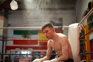 Boxer sitting in corner of boxing ring, exhaustedの写真素材 [FYI03555242]