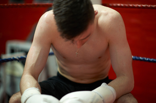 Boxer sitting in corner of boxing ring, exhaustedの写真素材 [FYI03555244]