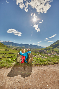 Mature couple sitting by roadside, looking at view, rear view, Meran, South Tyrol, Italyの写真素材 [FYI03555315]