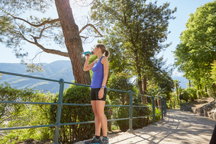 Young woman standing on rural pathway, looking at view, drinking from water bottle, Meran, South Tyrの写真素材 [FYI03555343]