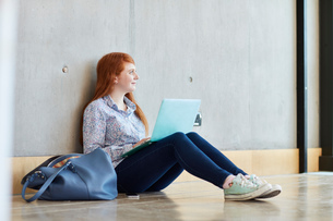 Young female student sitting on floor with laptop at higher education collegeの写真素材 [FYI03555367]