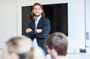 Portrait of male lecturer with arms folded in higher education college classroomの写真素材 [FYI03555381]