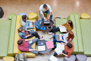 Overhead view of seven male and female students brainstorming in higher education college study spacの写真素材 [FYI03555396]