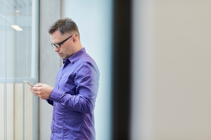 Male designer reading smartphone text in design studioの写真素材 [FYI03555409]
